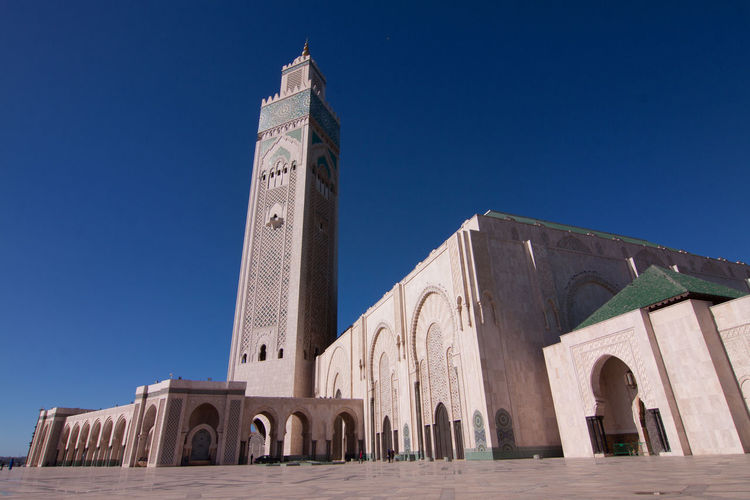 Low angle view of mosque hassan ii against blue sky