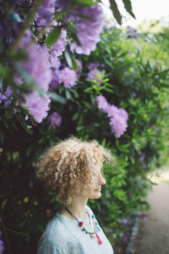 Woman Standing Against Purple Flowering Plants