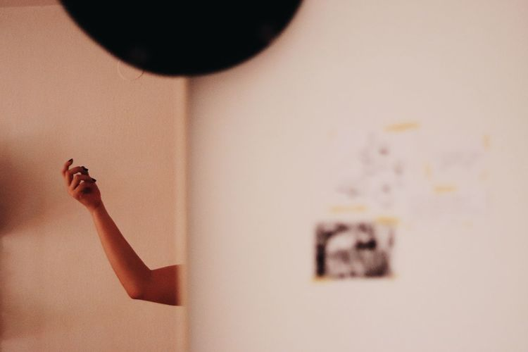 Close-up of woman hand on wall at home