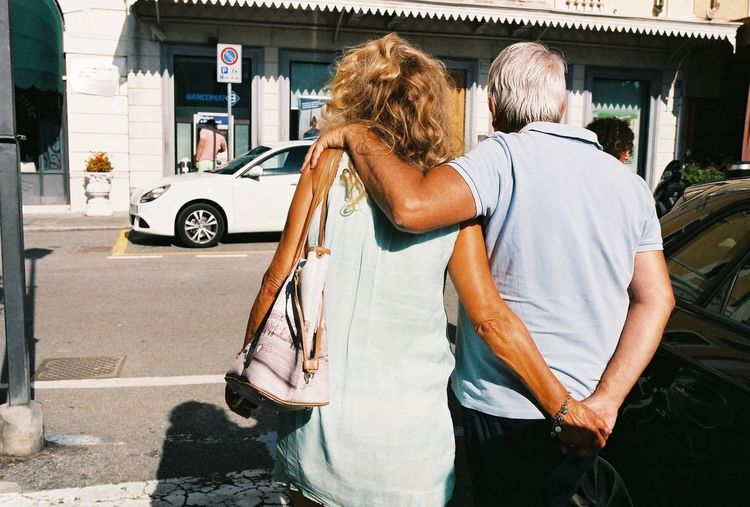 Rear View Of Senior Couple Walking On Street In City