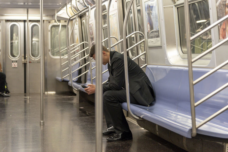Businessman alone on a subway car, sitting and scrolling through his smart phone device.