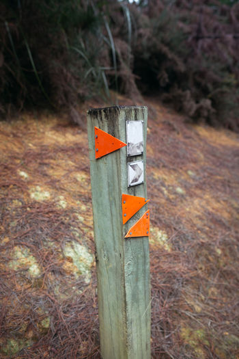 Close-up of information sign on wooden post in field