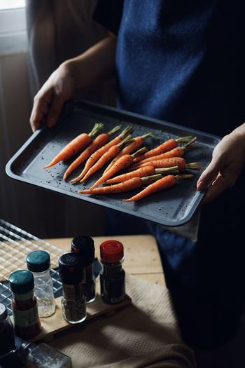 Midsection of woman holding carrots in tray at home
