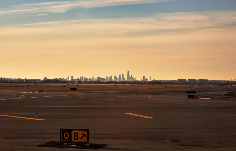 Manhattan skyscraper from the airport runway Manhattan Runway Silhouette Air Vehicle Airplane Airport Airport Runway Buildings Cloud - Sky Day Nature No People Outdoors Road Runway Sky Skyscraper Sunset Transportation Travel Destinations Airport Terminal Airfield Orange Color Urban Skyline Office Building