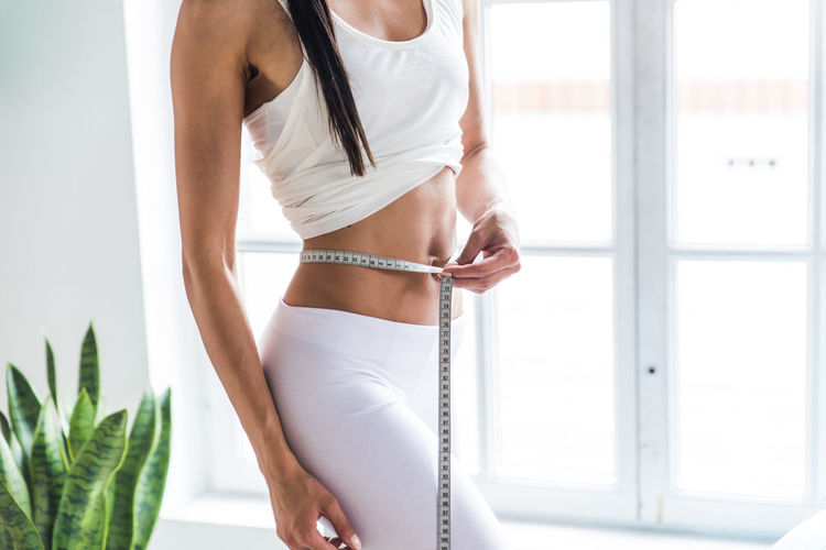 Midsection of woman measuring waist at home