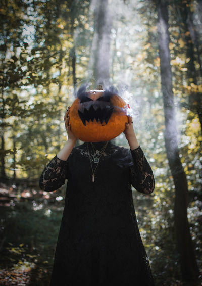 Woman wearing jack o lantern standing in forest