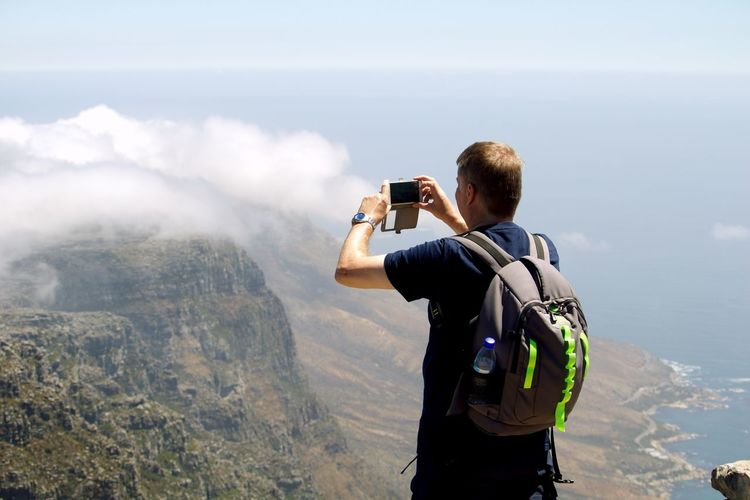 Rear view of man photographing standing against mountain range