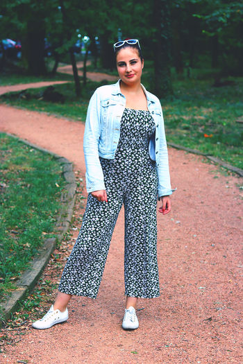 Full length portrait of young woman standing at park