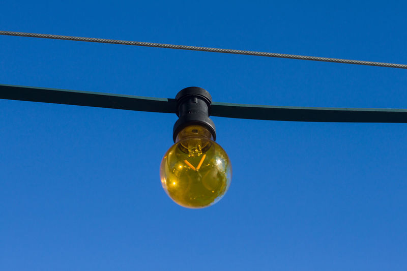 Electricity  Lighting Equipment Low Angle View Blue Light Bulb Clear Sky Cable No People Sky Hanging Electric Light Illuminated Light Close-up Connection Bulb Filament Single Object Fuel And Power Generation Power Supply Blue Background Directly Below
