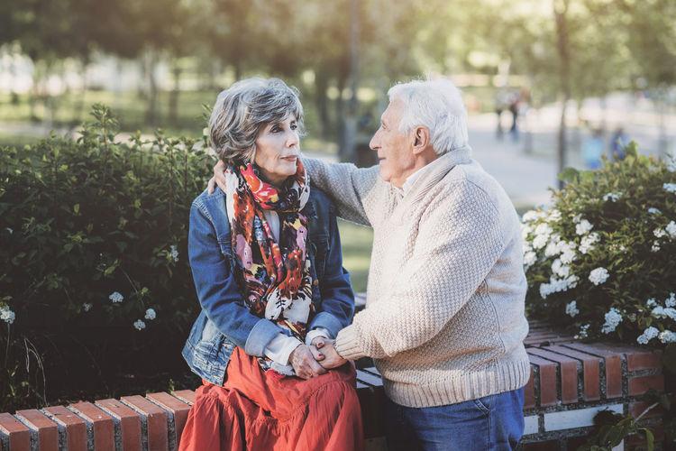 Senior adult embracing at park