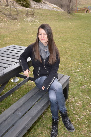Young woman sitting on bench in park
