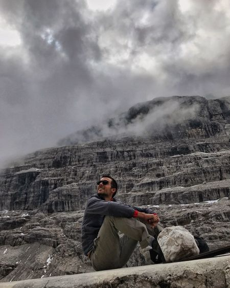 Low Angle View Of Young Man Sitting On Mountain Against Cloudy Sky