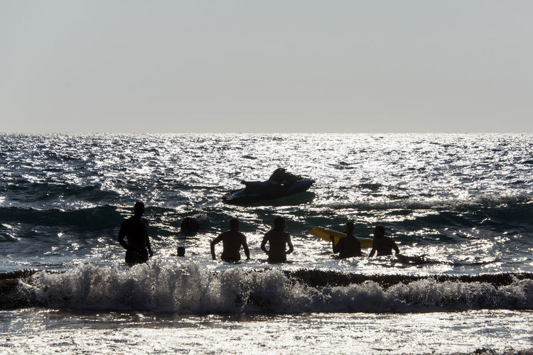 Silhouette of People playing, swimming in the waves in the island of Patmos, Greece in summer time Aquatic Sport Beach Beauty In Nature Clear Sky Day Group Of People Horizon Horizon Over Water Land Leisure Activity Men Motion Nature Outdoors Real People Sea Sky Sport Water Wave