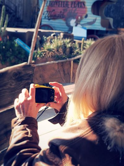 Midsection of woman photographing with mobile phone
