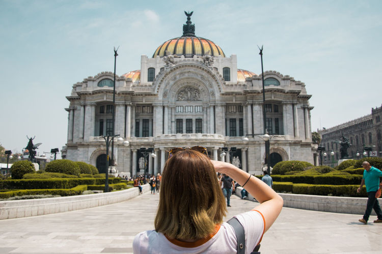 Rear view of woman in front of historical building against sky in city