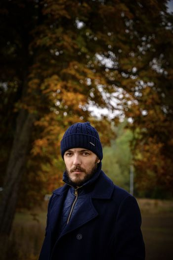 Portrait of man standing against trees in winter