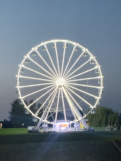 Low angle view of illuminated ferris wheel on field against sky at night