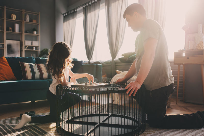 Girl Playing Checkers With Father On Table At Home