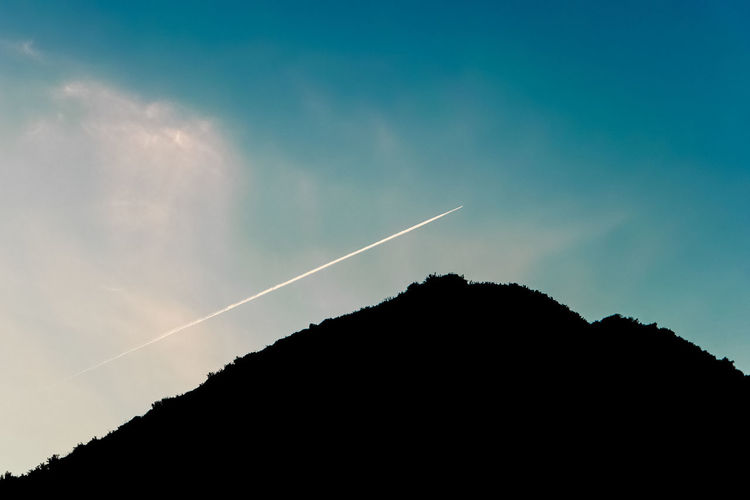 vapour trail over mountain Aerial View Airplane Atmosphere Atmospheric Mood Blue Blue Hour Cloud Flying Landscape Majestic Silhouette Silhouette Sky Tranquil Scene Traveling Vapour Trail