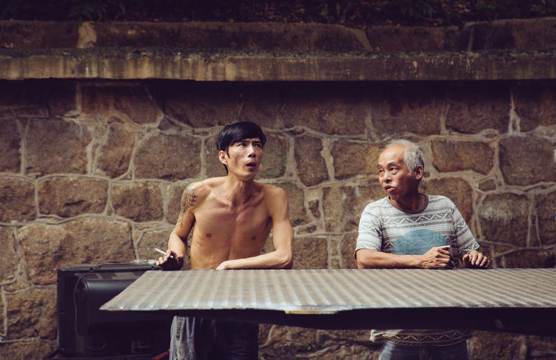 Hong Kong Streets Hong Kong Hong Kong City Adult Bench Bonding Brick Brick Wall Casual Clothing Couple - Relationship Front View Males  Men People Real People Sitting Streetphotography Teenage Boys Three Quarter Length Togetherness Two People Wall Women Young Adult Young Men
