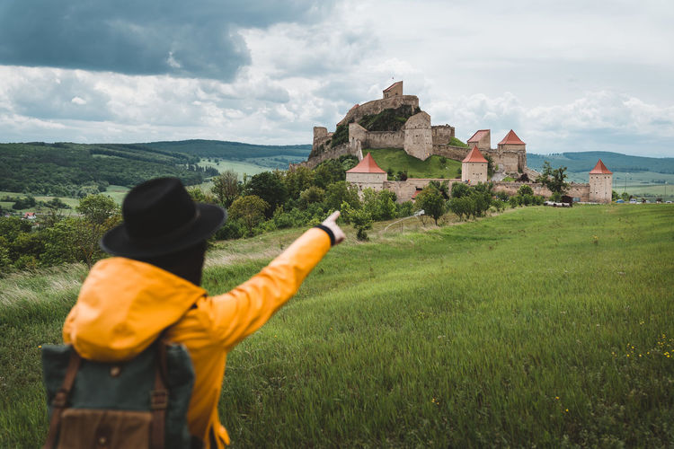 Rear view of woman gesturing over castle while standing on grass