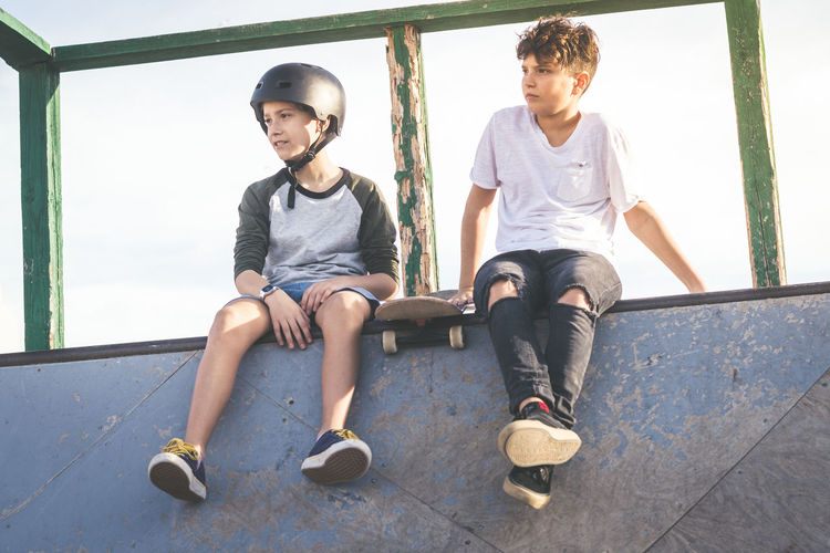 Low angle view of boys sitting on wall against sky