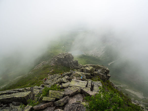 A steep rocky section of the Cathedral Trail on Katahdin in Baxter State Park, Maine, low clouds and fog obscuring the valley, hikers ascending the rocks. Fog Mountain Scenics - Nature Nature Beauty In Nature Rock Environment Outdoors Rock - Object Landscape Katahdin Baxter State Park Maine Hiking Trail Climbing Boulder Clouds Mountain Peak Valley Adventure High Up Extreme Terrain Wilderness Mountain Ridge