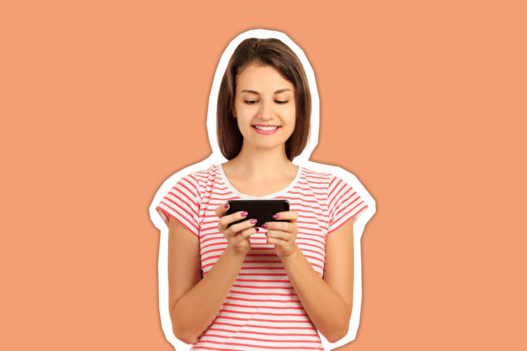 Portrait of a smiling young woman photographing against orange background
