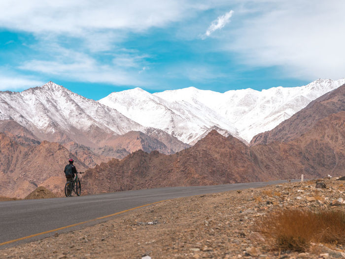 Rear View Of Man With Bicycle By Mountains