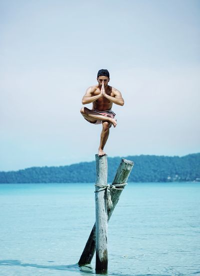 Man Doing Yoga On Wooden Post In Sea