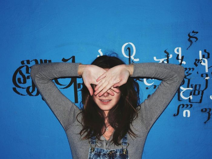 Teenage girl covering face with hands standing against wall