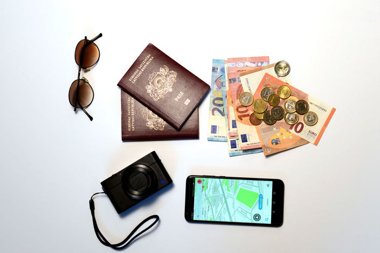 Sunglasses, smartphone, passports, camera and money isolated on a white background. Tourism concept. Dollar Money Cash Savings Banking Finance Bill Currency Wealth Background Banknote Bussiness Profit Green Close-up USD Exchange Loan  Paper Sign Payment Pay Stack Number Textured  Abstract Earnings Symbol Capital Assets Sunglasses Camera Phone Smart Phone Passports Passport Navigation Euro Coins Tourism Travel Concept Isolated White Background Studio Shot Indoors  Still Life Technology Directly Above Large Group Of Objects No People High Angle View Communication Wireless Technology Variation Photography Themes Choice Digital Tablet Connection Text Representation Stapler