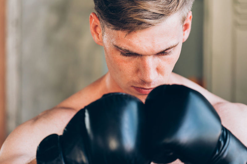 Close-up of confident young woman with boxing gloves in gym