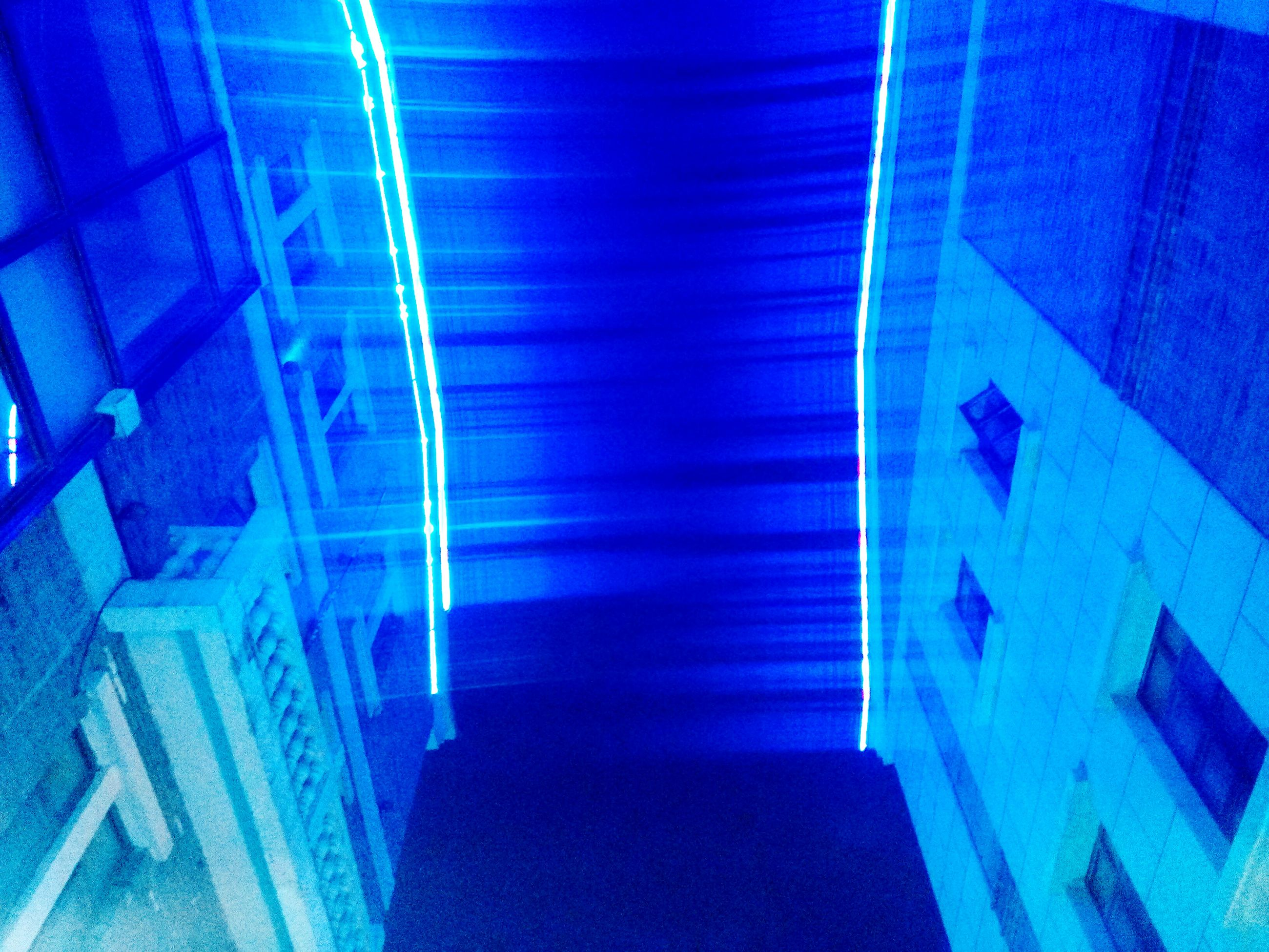 illuminated, indoors, blue, architecture, built structure, lighting equipment, ceiling, light - natural phenomenon, night, glowing, low angle view, pattern, wall - building feature, modern, electric light, sunlight, light, building, light beam, no people
