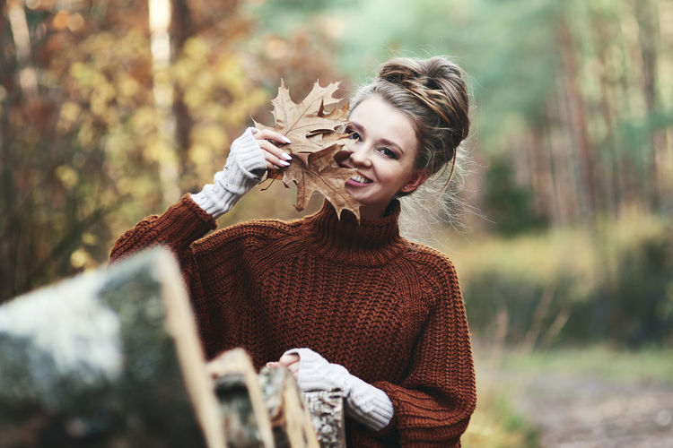 Portrait of smiling young woman holding plant