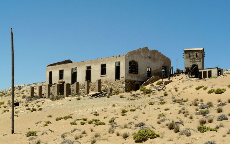 Abandoned built structure against clear blue sky