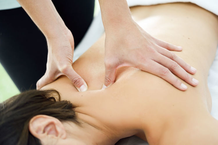 Young woman receiving a back massage in a spa center. Female patient is receiving treatment by professional therapist. Back Center Hands Physio Relaxing Shoulder Therapy Woman Beauty Female Girl Massage Massage Therapy Massages Massaging Physiotheraphy Physiotheraphyst Relax Relaxation Spa