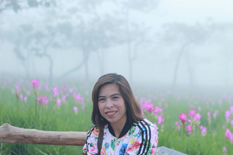 Portrait of smiling woman in forest during foggy weather