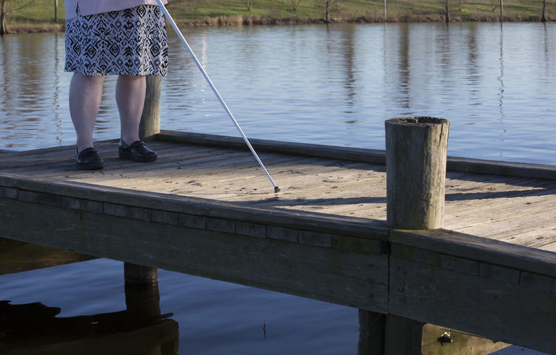 Low section of blind woman standing on pier over lake