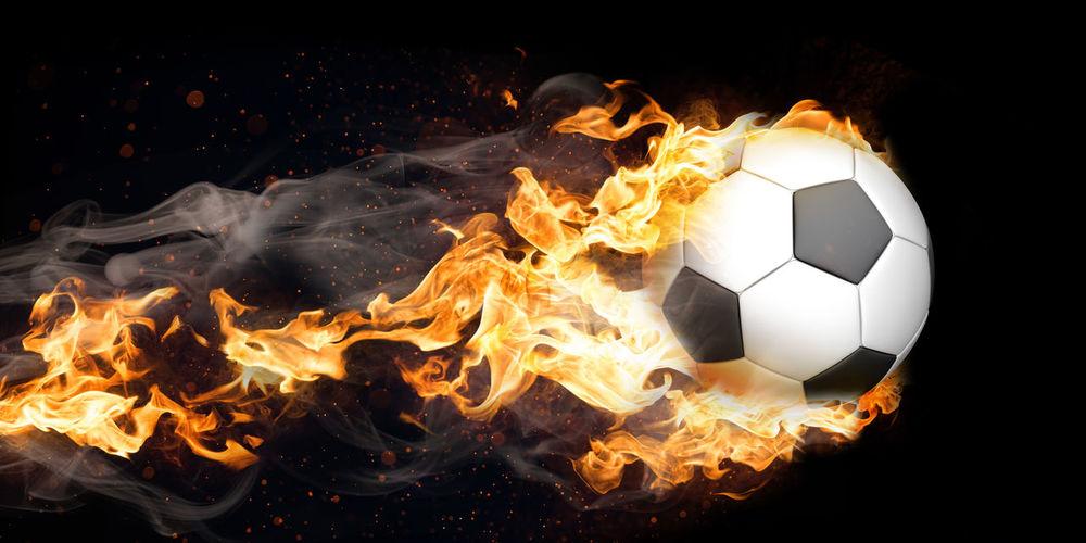 Digital composite image of burning soccer ball in motion against black background