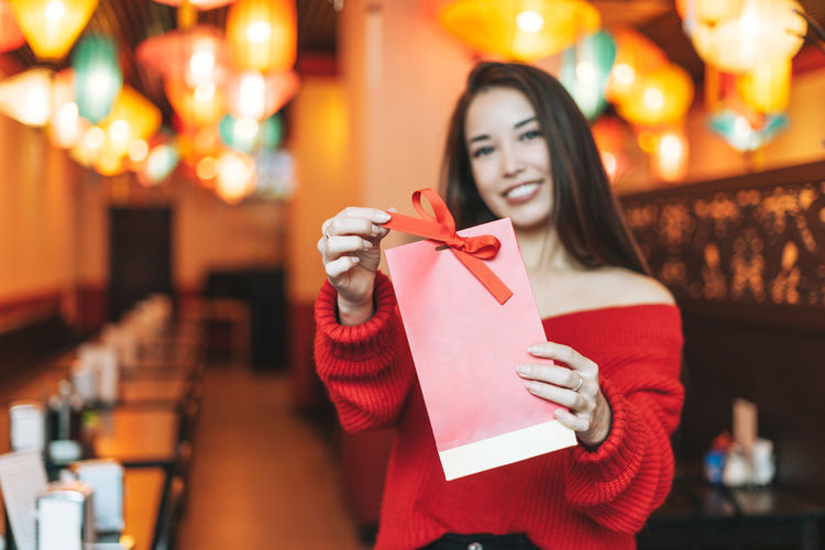 Beautiful young asian woman in red clothes with red gift bag in restaurant celebrating