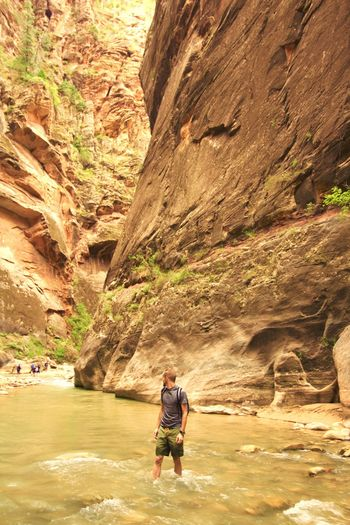 Man Standing In River Against Mountains At Zion National Park