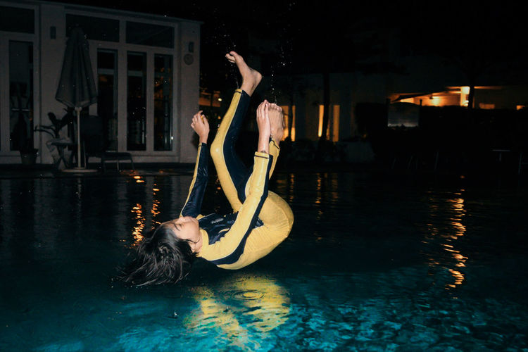 Freeze Motion Water Night Real People Skill  Performance Lifestyles Swimming Pool Women Pool Adult Dancing People Reflection Arts Culture And Entertainment Young Adult Full Length Leisure Activity Nature Arms Raised Human Arm Beautiful Woman Flash Photography Springtime Decadence