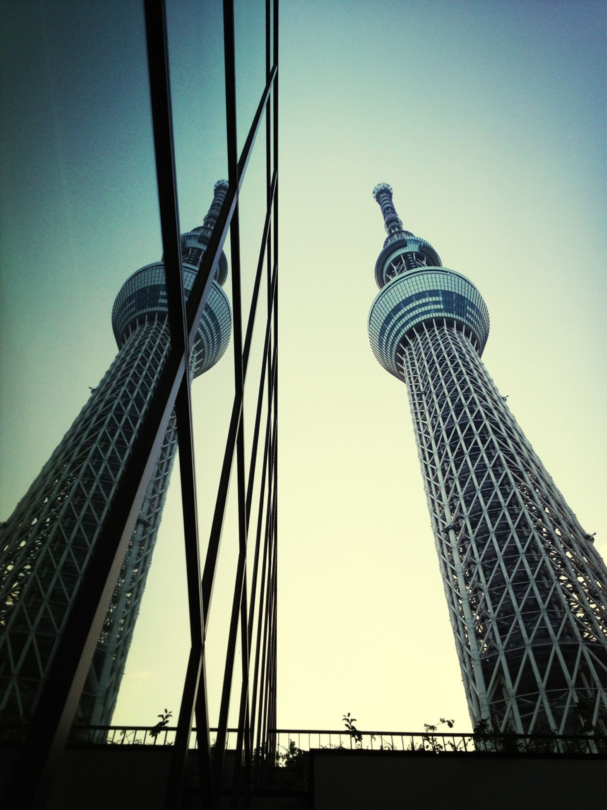 built structure, architecture, tower, low angle view, tall - high, international landmark, famous place, travel destinations, capital cities, tourism, building exterior, clear sky, travel, city, communications tower, skyscraper, eiffel tower, metal, tall, sky