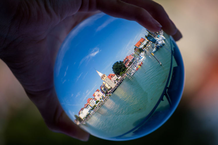 Person holding crystal ball with reflection of city