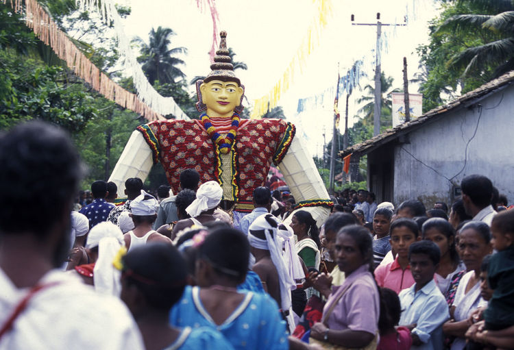 People By Sculpture On Street During Traditional Festival In Village