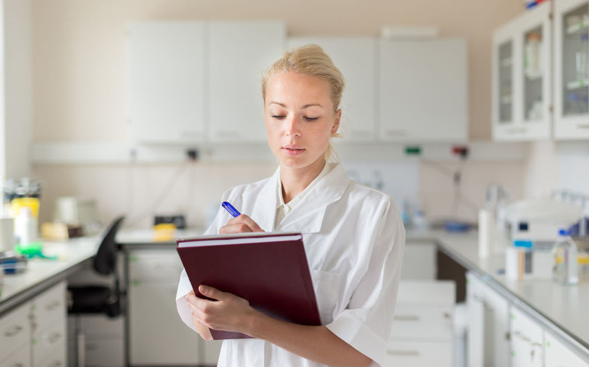 Beautiful woman writing in diary while standing at laboratory