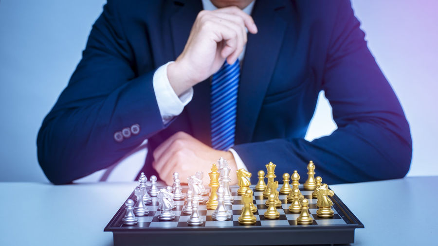 Low angle view of man playing with chess against the background