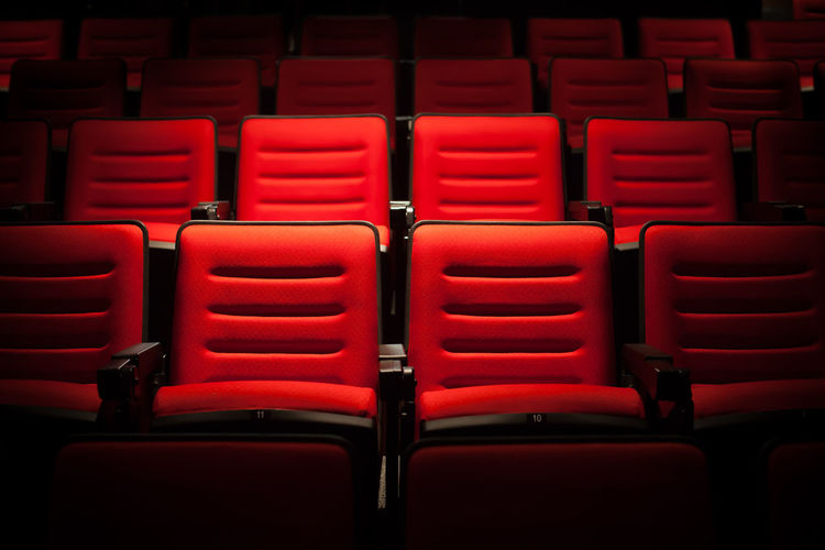 Red seat in the movie theater. Blurry background. Absence Arrangement Auditorium Backgrounds Chair Day Empty Film Industry In A Row Indoors  Movie Theater No People Red Repetition Seat