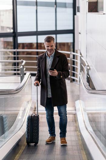 Full length of man using mobile phone in bus